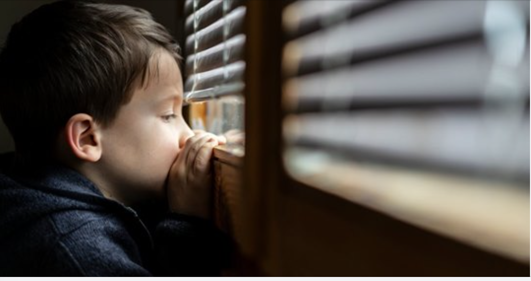 Young boy looking through the blinds of a window