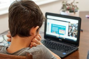 Young Boy staring at a laptop