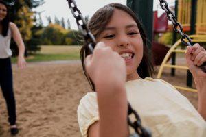 child smiles on swingset - Families as Allies
