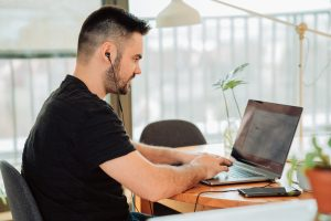 A man sits in front of a laptop