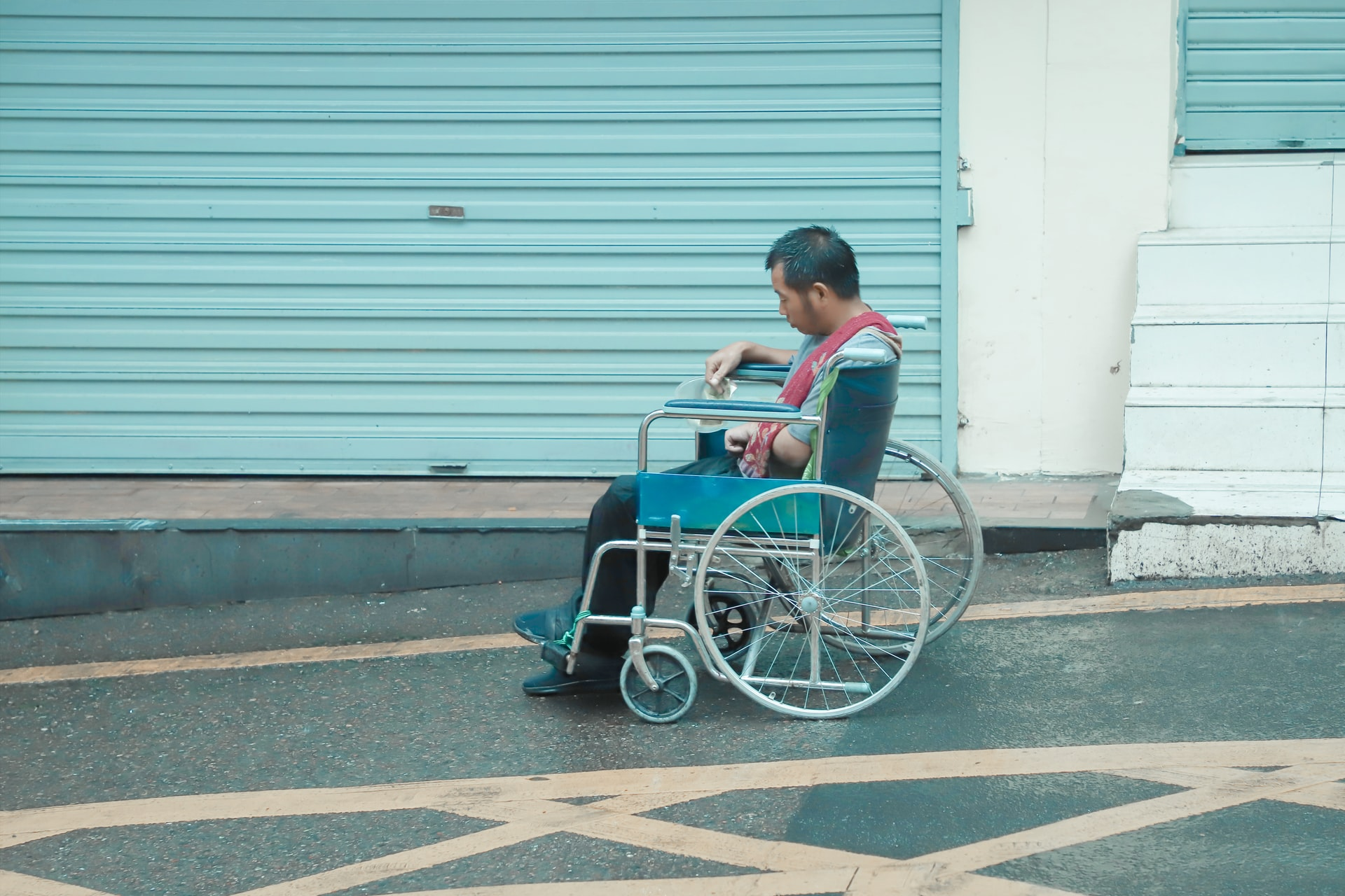 A man sits in a whhelchair alone on the side of a street