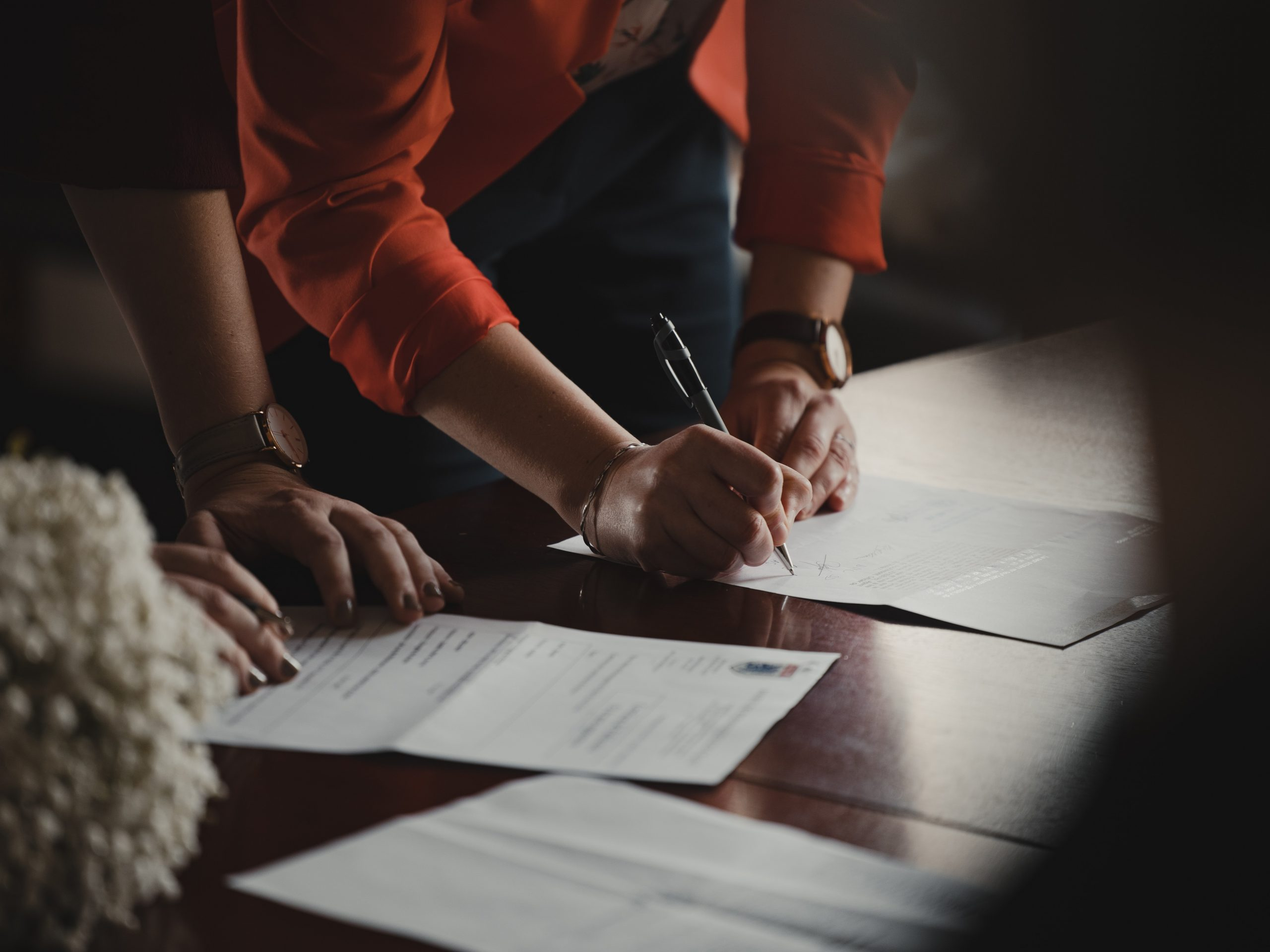 Two people look over and sign paperwork on a table