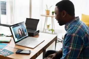 A man sits in fron tof an open laptop and talks virtually to a woman on the screen